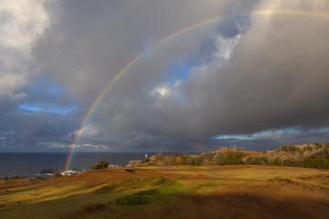 A Rainbow touches down on the west maui coastline.
