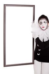 Weiblicher Clown zeigt auf einen leeren Rahmen