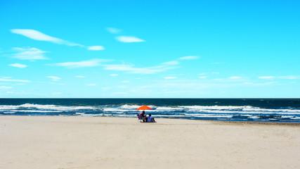 Beach summer couple under a orange umbrella
