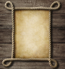 Wall Mural - aged paper with rope frame on old wood background