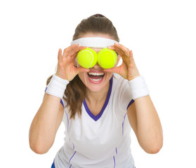 Happy tennis player holding balls in front of eyes