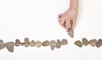 Hand schiebt Stein in Linie