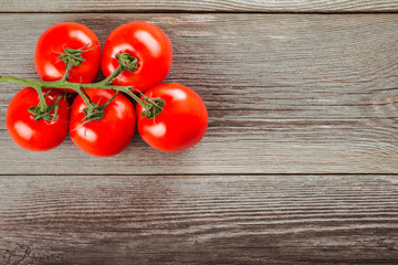 Fresh tomatoes on the old wooden table. Tomatoes on a branch.