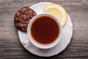 Hot cup of tea in white mug with lemon and chocolate cookie.