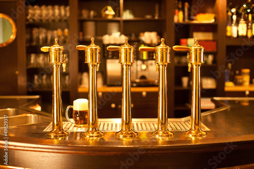 Wall mural Luxury gold beer spigot at the brewery with a glass of beer