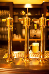 Fototapete - Luxury gold beer spigot at the brewery with a glass of beer