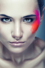 cute woman with coloured powder on face