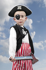 young boy in pirate costume outdoors
