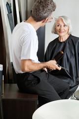 Hairdresser Examining Customer's Hair At Parlor