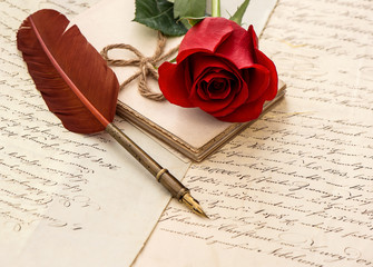 red rose flower, old letters and antique feather pen