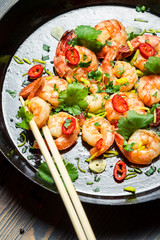 Closeup of shrimps with herbs on pan