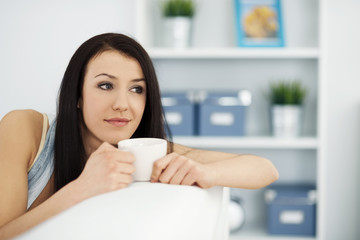 Beautiful woman on couch with cup of coffee