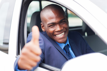 happy african businessman giving thumb up inside new car