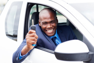 happy african vehicle buyer inside his new car with car key