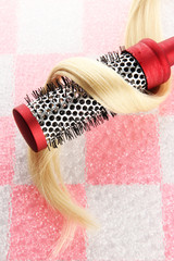 comb brush with hair on pink  tile wall background