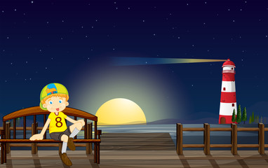 A boy sitting at the bench in the middle of the night