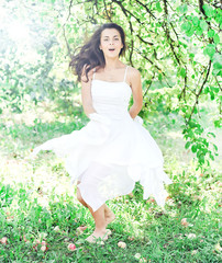 Beautiful young woman dancing in the morning bright summer orcha