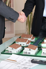 Handshake over a model housing estate