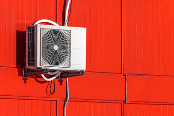 Airconditioning unit on a red wall
