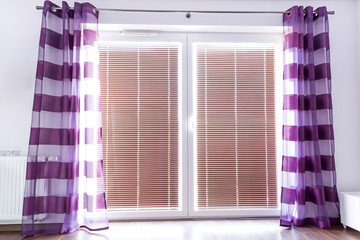 Balcony window with purple curtains