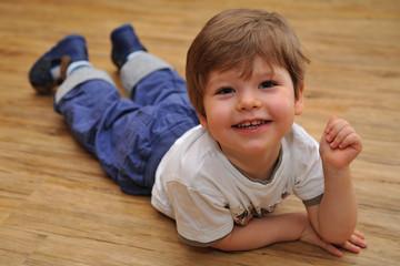 Happy small boy lying on wooden floor
