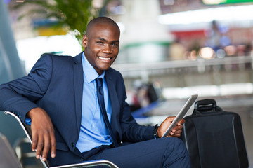 handsome african businessman using tablet computer in airport