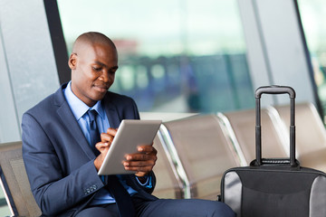 black businessman using tablet computer at airport