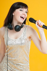 Carefree young woman singing with a microphone, studio shot