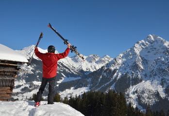 Skifahrer jubelt vor alpiner Kulisse