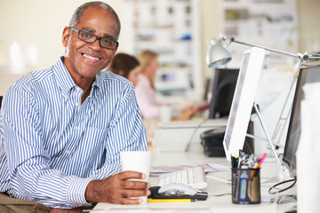 Man Holding Cup Working At Desk In Busy Creative Office