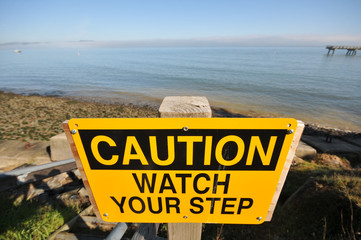 Caution Watch Your Step sign by the ocean