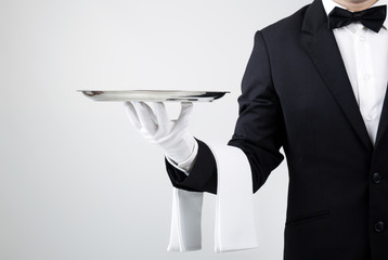 Fototapeta Waiter holding empty silver tray over gray background obraz
