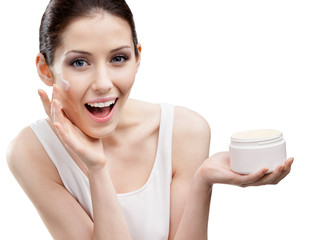Woman applying emollient cream from container on face