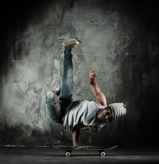 Young b-boy man doing brake dancing movements on skateboard