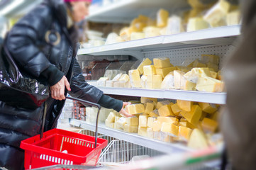 Customer select cheese pieces on shelves in supermarket