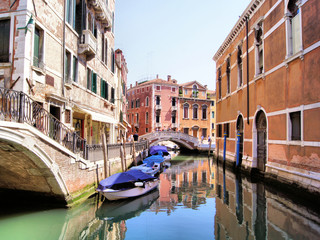 Beautiful canals of Venice with boats and reflections