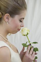 Portrait d'une jeune mariée de profil tenant une rose jaune