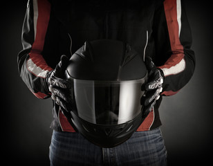 Fototapete - Motorcyclist with helmet in his hands.  Dark background