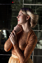 Portrait of pretty blonde in golden dress