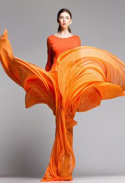 beautiful woman in long orange dress posing in the studio