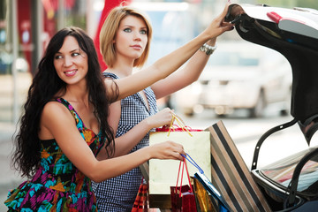 Two young women with a shopping bags