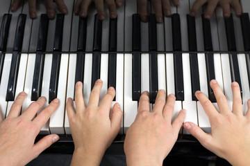 Quatre mains jouant du piano