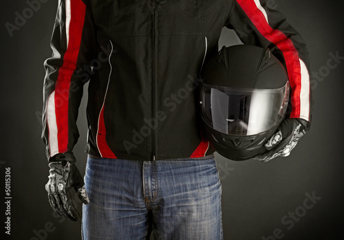 Fototapete Biker with helmet in his hands. Dark background