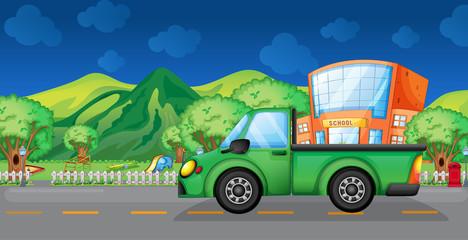 A green truck near the school