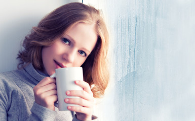 beautiful dreamy young woman with a cup of hot coffee at the win