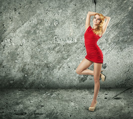Beautiful Woman in Red Dress on Wall Background