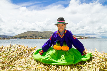 Sitting girl on a floating Uros island, Titicaca