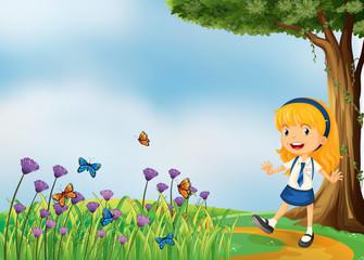 Keuken foto achterwand Vlinders A young school girl in the garden with butterflies