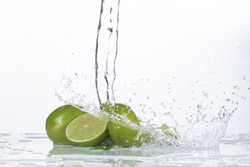 lime with leaf splashing into clear water