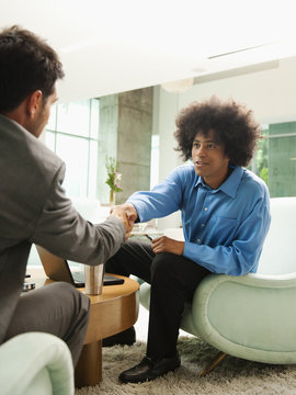 Businessmen snaking hands in lobby